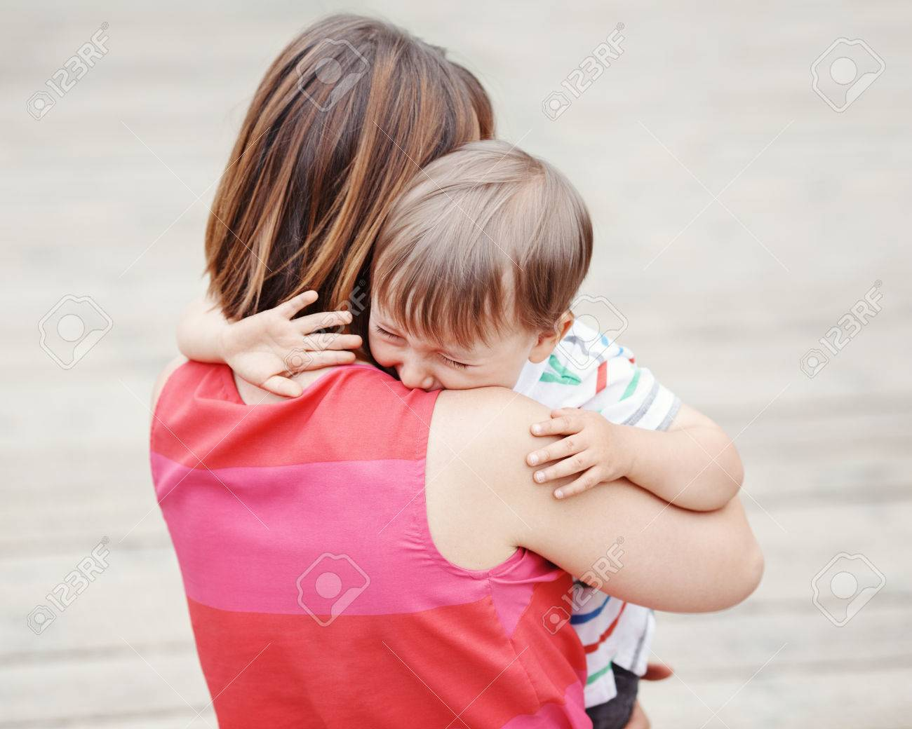Portrait of young Caucasian woman mother comforting her crying little toddler boy son outside in park on summer day, parenthood lifestyle concept - 64432787