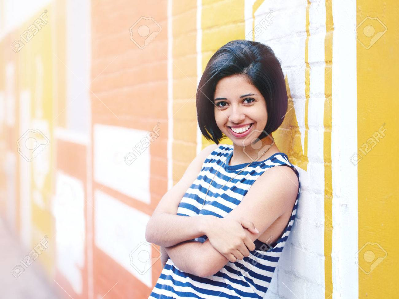 Portrait of beautiful smiling young hipster latin hispanic girl woman with short hair bob, in blue white striped tshirt, leaning on brick wall in city looking in camera - 64481692