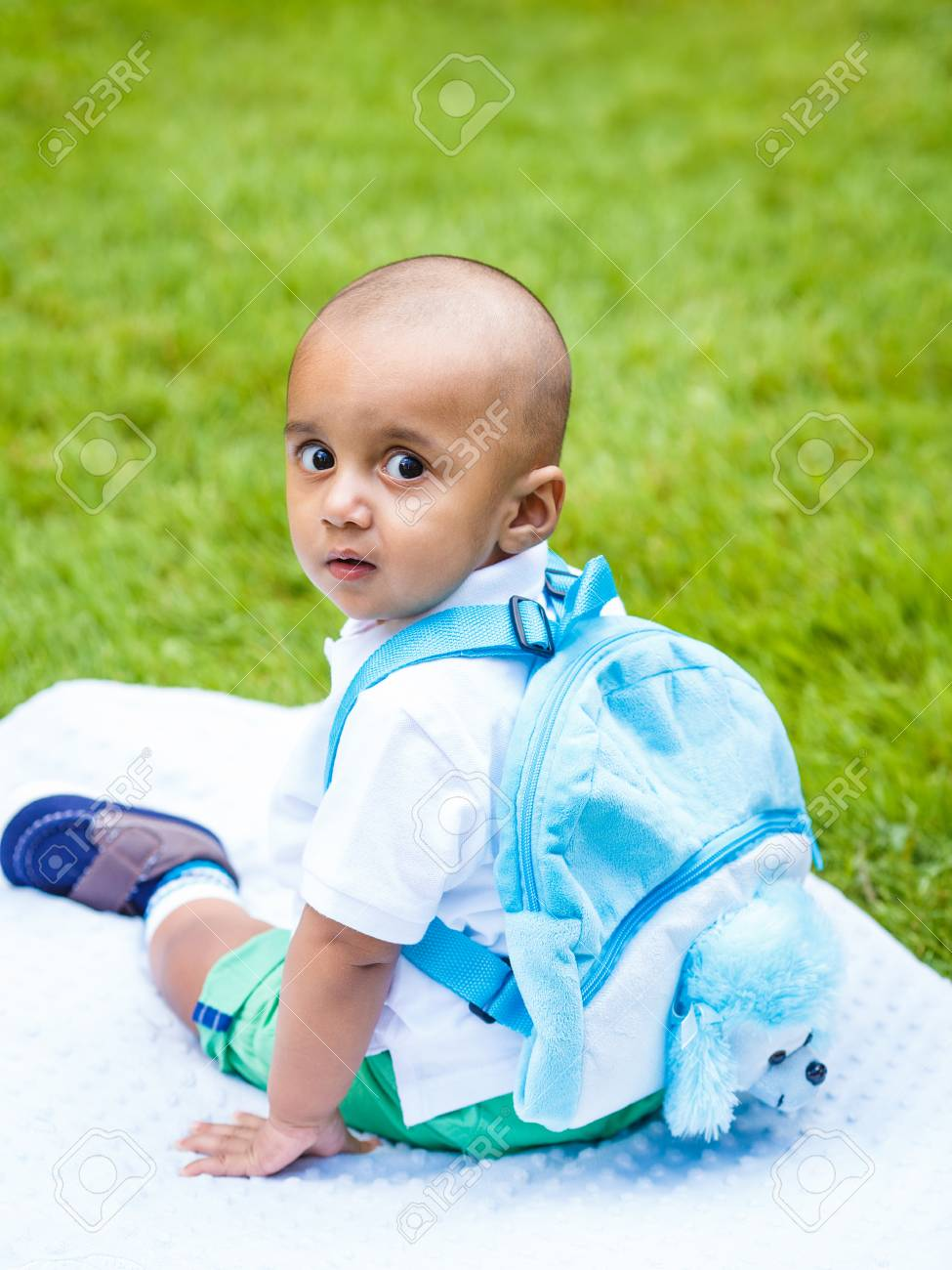 20e81f2756c Portrait of cute adorable little indian mixed race infant boy in white  shirt sitting on ground