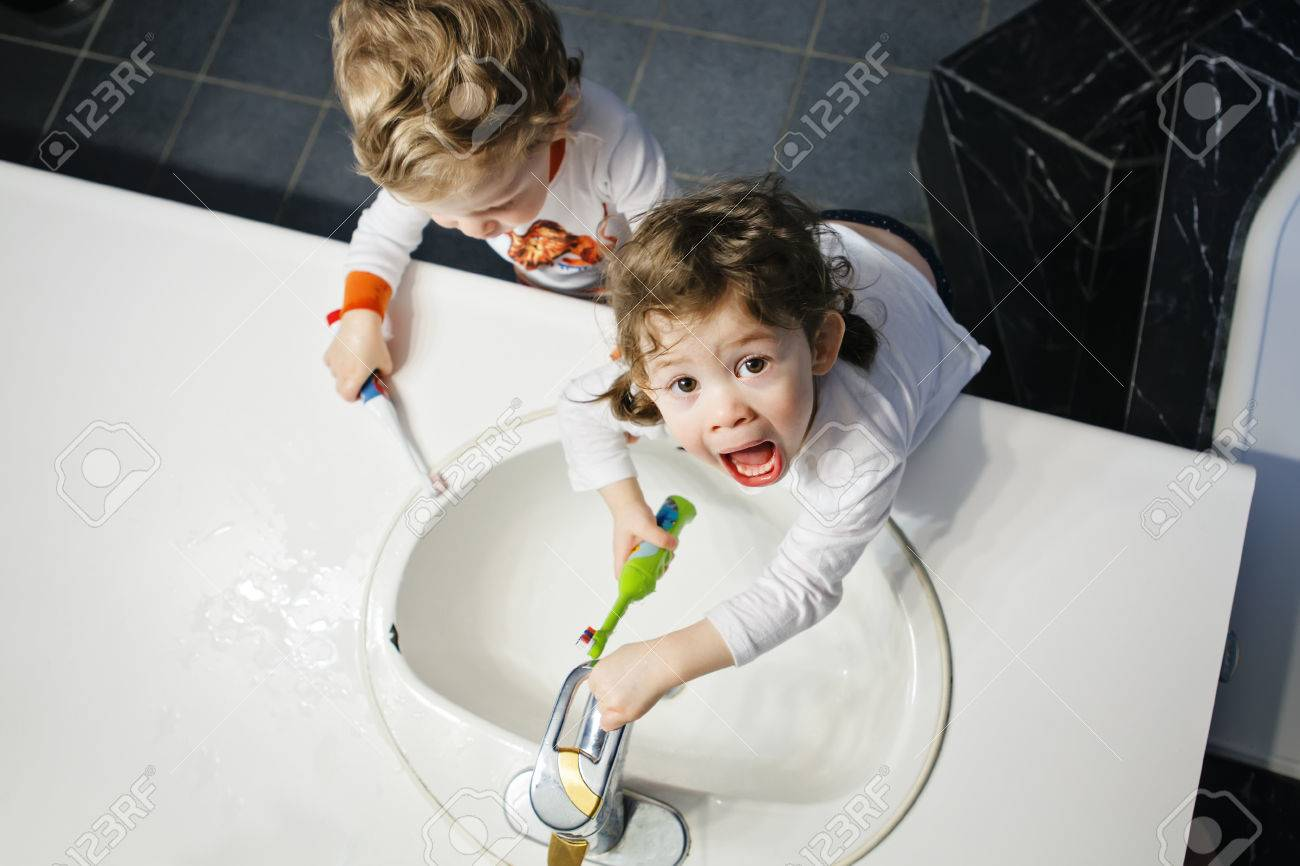 Closeup portrait of twins kids toddler boy girl in bathroom toilet washing face hands brushing teeth with toothbrash playing with water, lifestyle home style, everyday moments, top view - 64550175