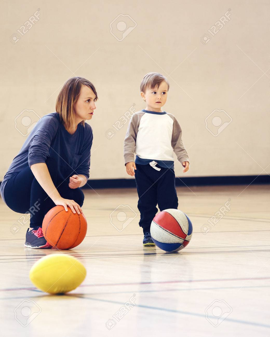 Mother and son playing with ball in gym, early child healthy development, family fun, coaching and training concept, - 64550182