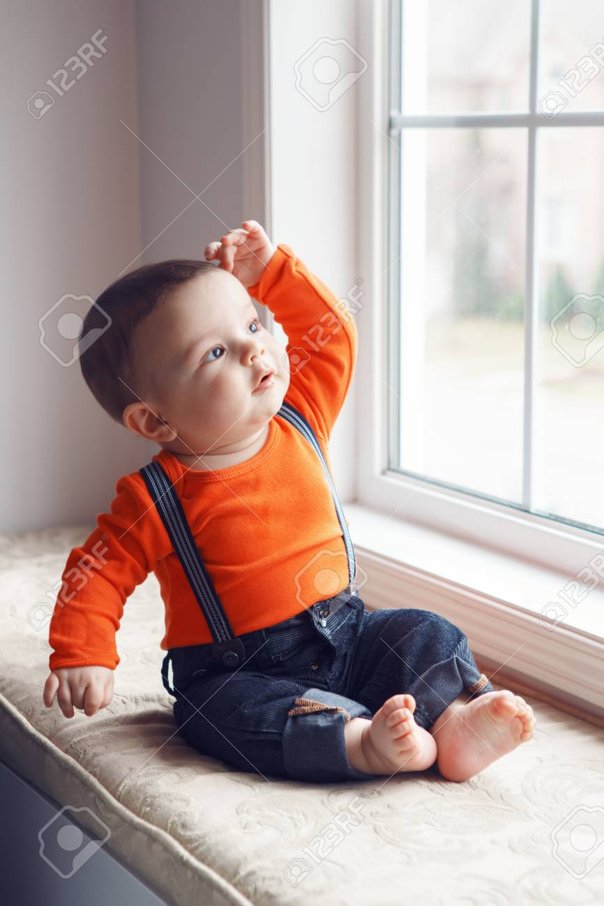 5adb8e80542dc Portrait of cute adorable stylish Caucasian baby boy with black eyes in  orange shirt