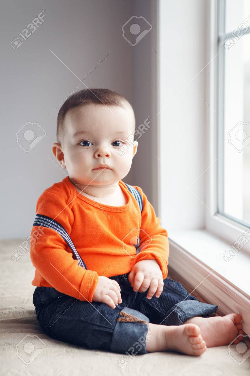 a4fa7a6d683e5 Portrait of cute adorable stylish Caucasian baby boy with black eyes in  orange red shirt