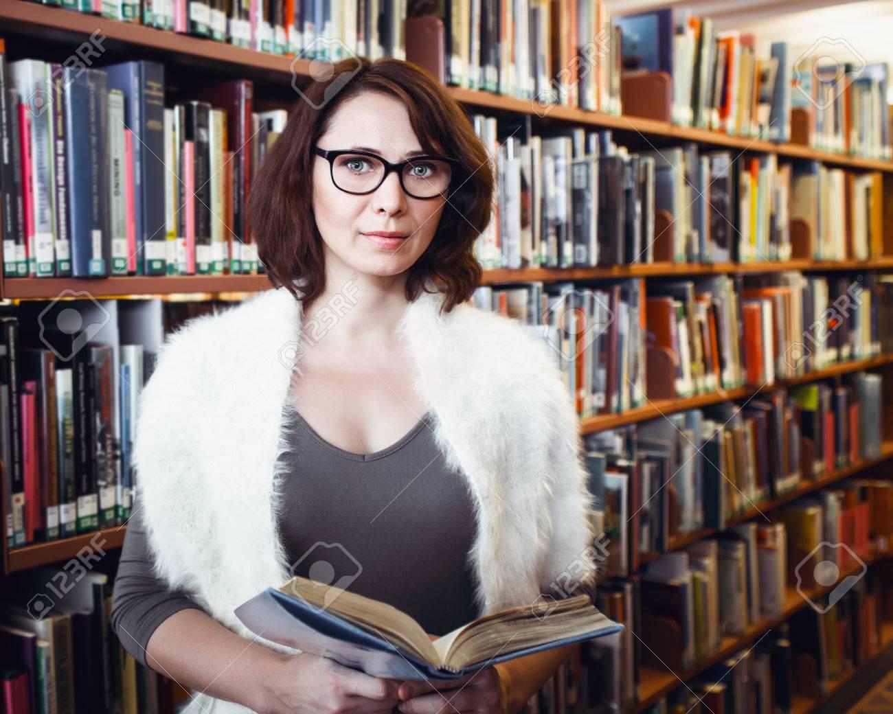 Archivio Fotografico - Ritratto di mezza età matura bruna studente donna  caucasica con gli occhiali in libro partecipazione biblioteca b5d36a1f2e6f