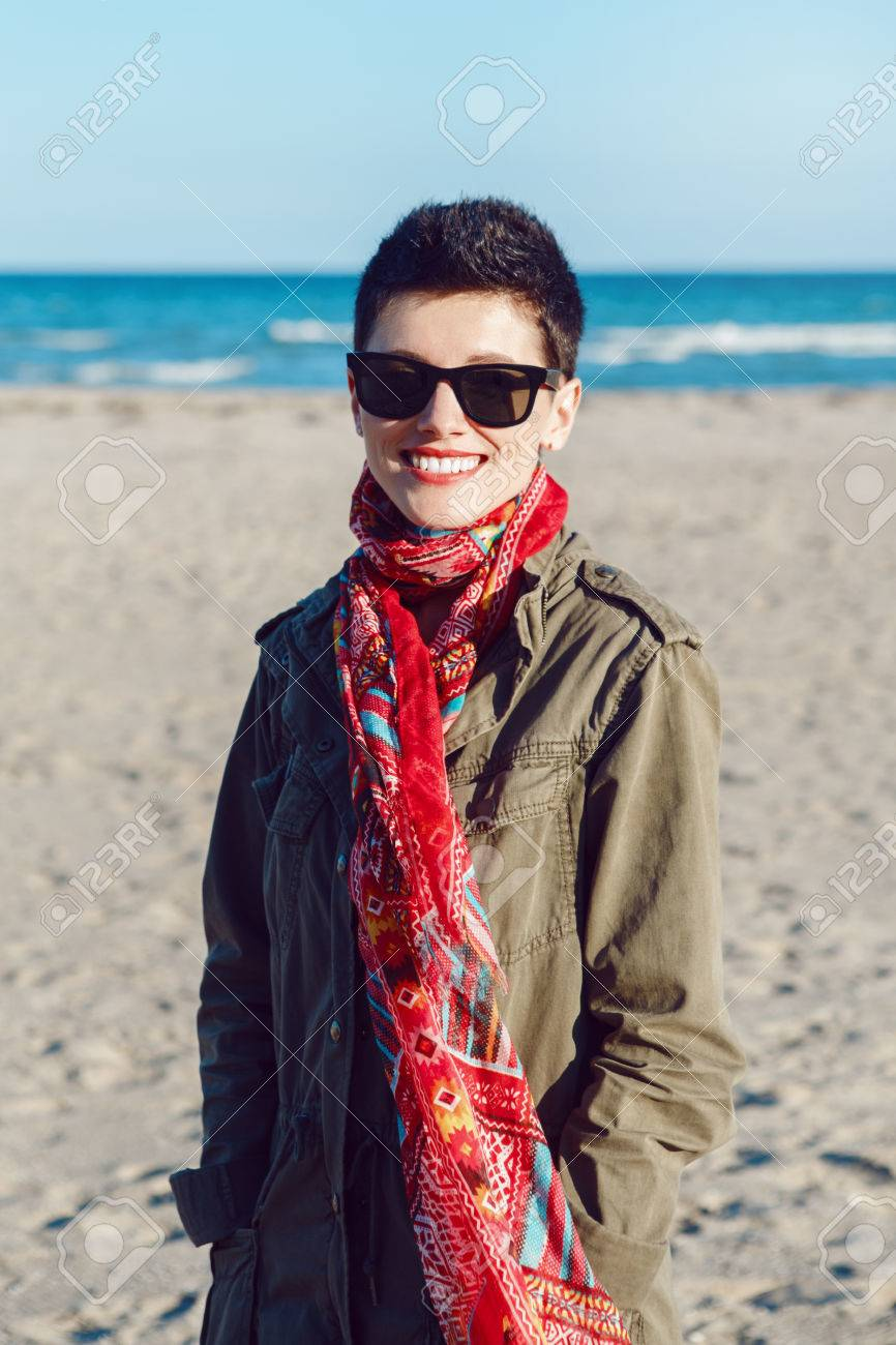 Portrait of happy smiling beautiful Caucasian white brunette woman with short hair in green jacket, red scarf and sunglasses, looking in camera, standing on sea ocean beach at sunset - 65635657
