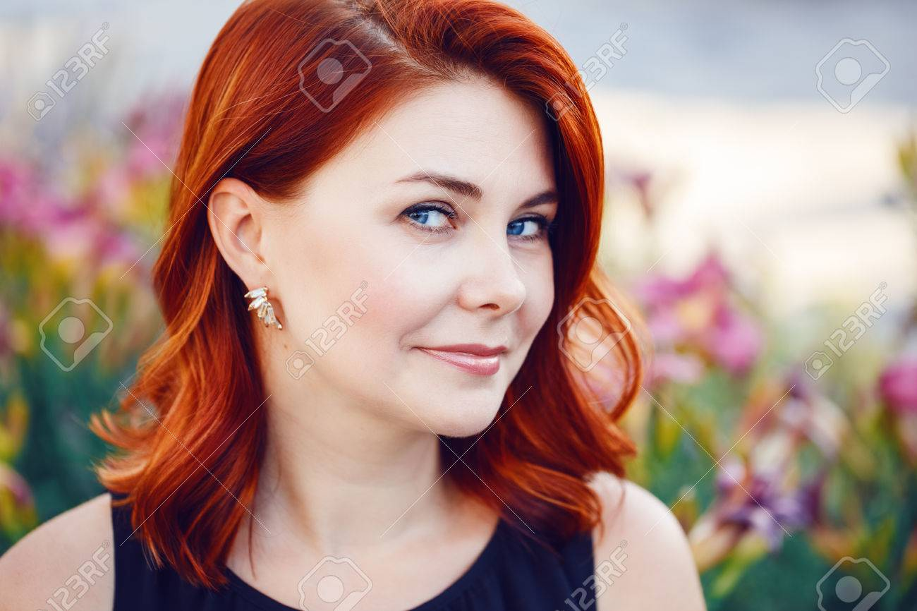 Closeup portrait of smiling middle aged white caucasian woman with waved curly red hair in black dress looking in camera outside in park among flowers - 65636196