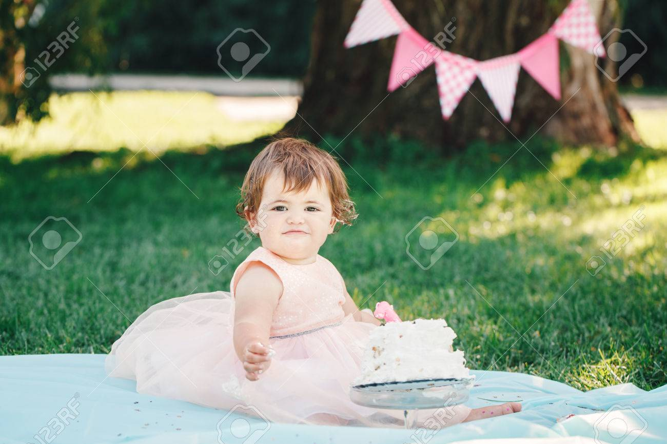 Portrait of cute adorable Caucasian baby girl with dark brown eyes in pink tutu dress celebrating her first birthday with gourmet cake looking in camera outside in park, cake smash - 65636356