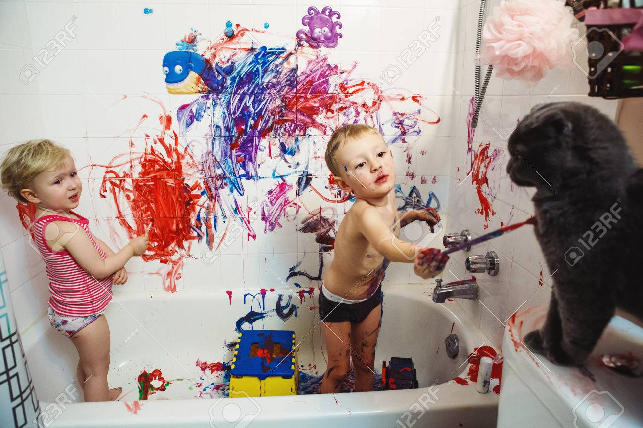 Portrait of two cute adorable white Caucasian little boy and girl playing painting cat with paints in bathroom having fun - 65636836