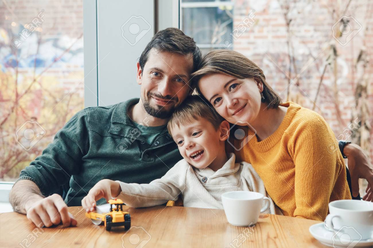 Portrait of white Caucasian happy family of three mother, father and son, sitting in restaurant cafe at table, smiling playing, authentic lifestyle - 72969292