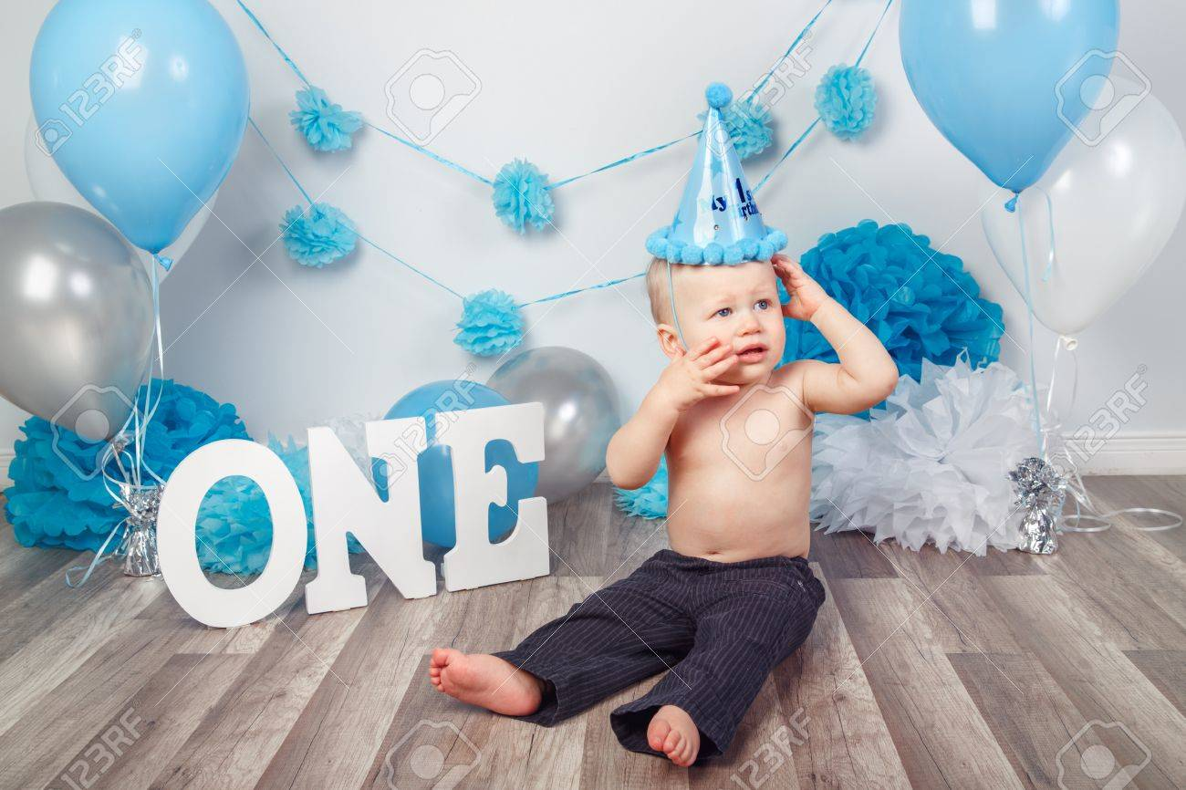 Portrait Of Adorable Caucasian Baby Boy With Blue Eyes In Dark Pants And Cone Hat Celebrating