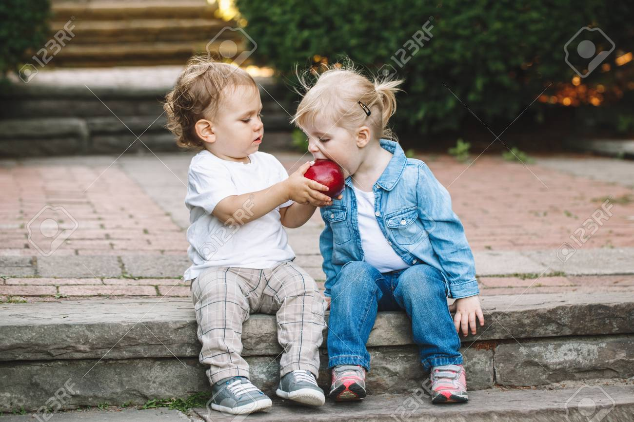 Group portrait of two white Caucasian cute adorable funny children toddlers sitting together sharing eating apple food, love friendship childhood concept, best friends forever - 76359202