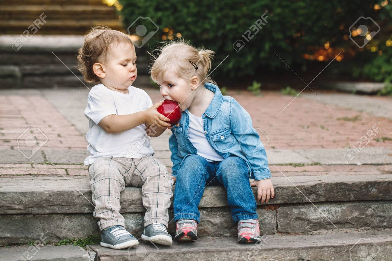 Group portrait of two white Caucasian cute adorable funny children toddlers sitting together sharing eating apple food, love friendship childhood concept, best friends forever - 76359198