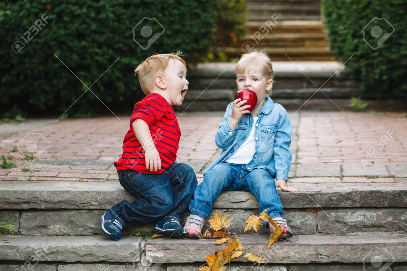 Group portrait of two white Caucasian cute adorable funny children toddlers sitting together sharing eating apple food, love friendship childhood concept, best friends forever - 76359256