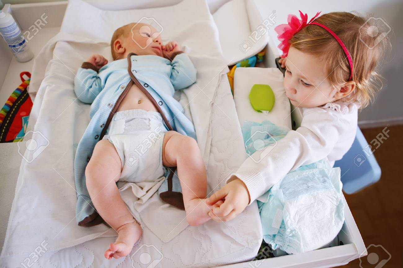 Lifestyle portrait of cute girl toddler helping her mother, changing baby diaper. Older sister looking at her little younger sibling brother. - 77838840