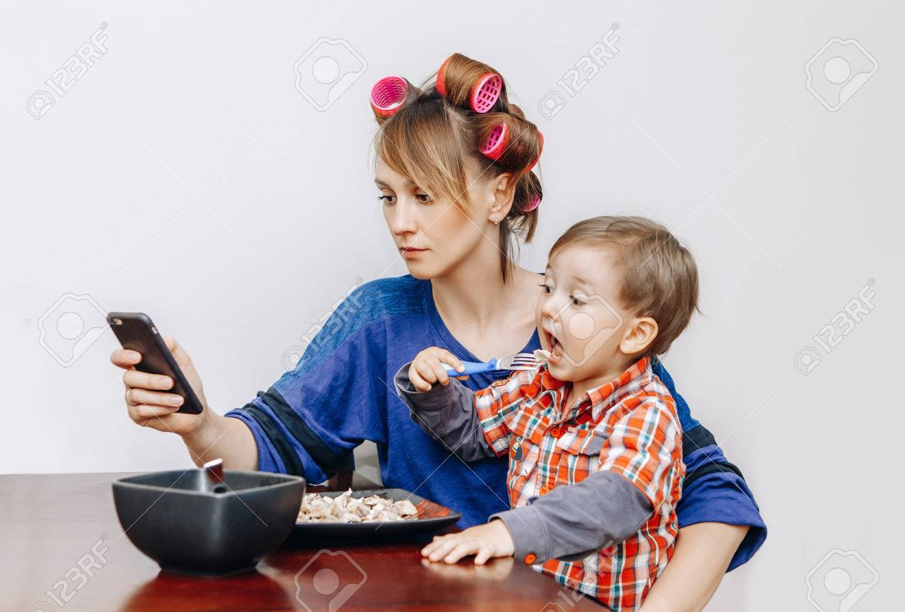 Busy tired white Caucasian young woman mother housewife with hair-curlers in hair looking on phone, surfing Internet, funny child son boy sitting eating meal lunch, white background - 78340558