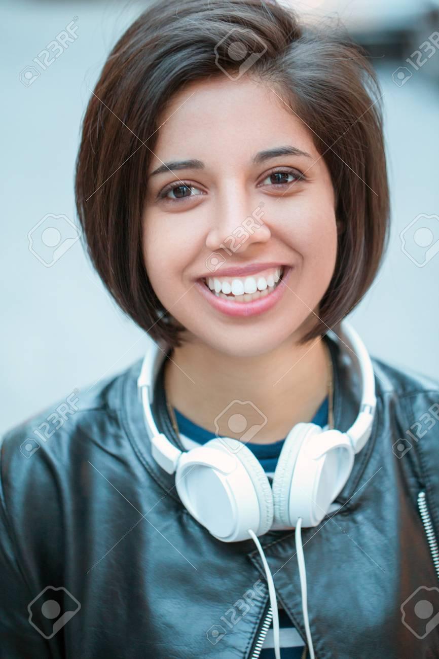 Portrait of beautiful hispanic latin girl woman short black hair in leather jacket with headphones
