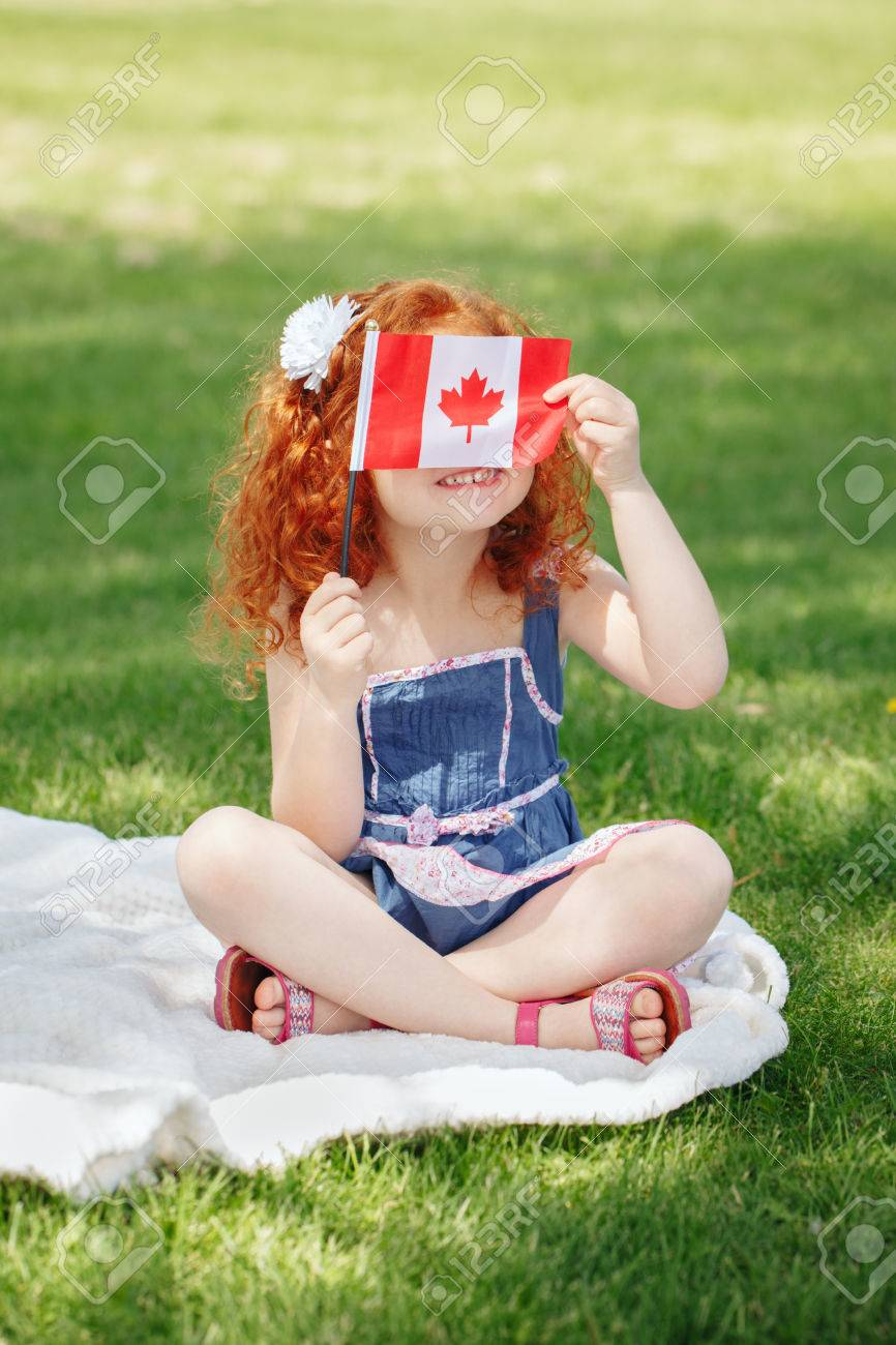 Portrait of cute little red-haired Caucasian girl child holding Canadian flag with red maple leaf, sitting on grass in park outside, celebrating Canada Day anniversary - 80170669