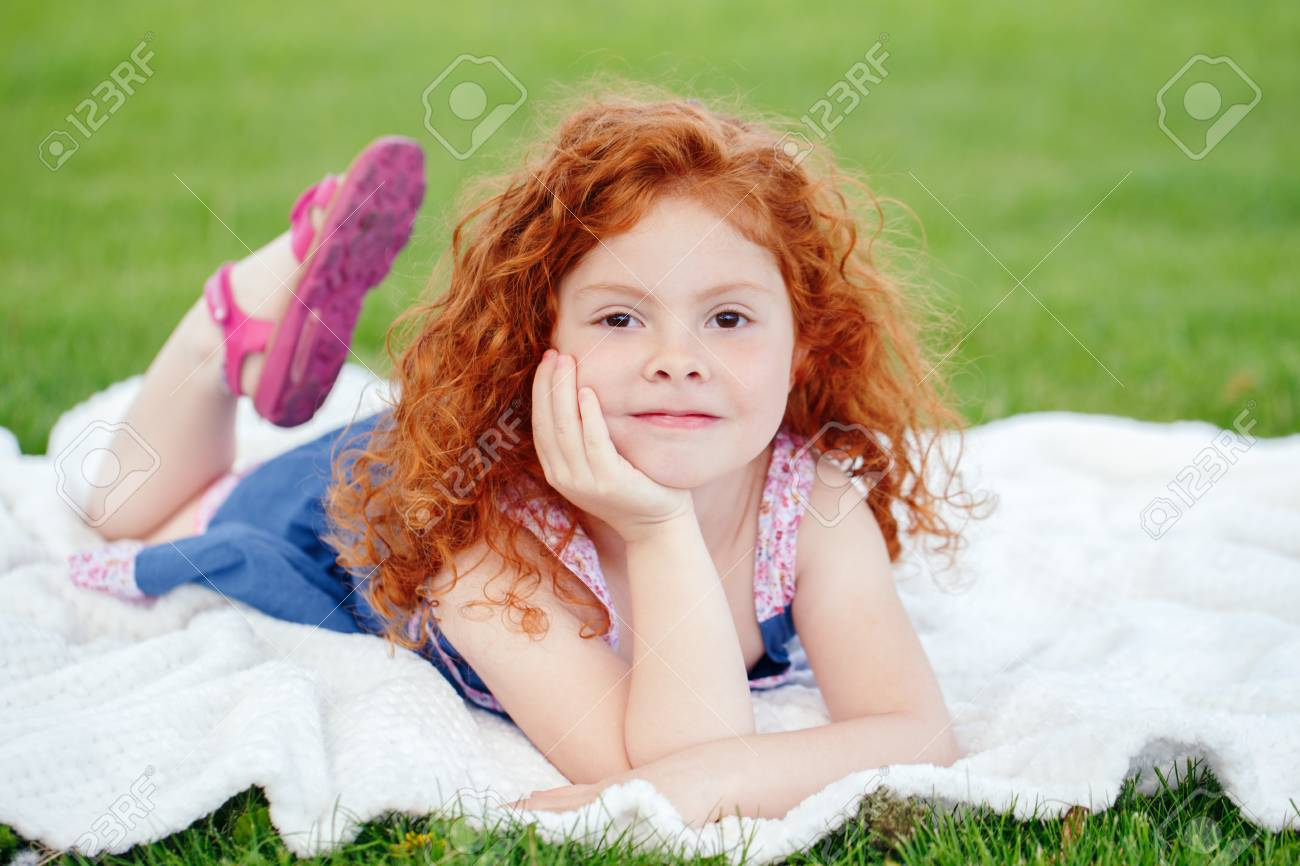 Portrait of cute adorable pensive little red-haired Caucasian girl child in blue dress lying on green grass in park outside, dreaming thinking, happy lifestyle childhood concept - 80930803