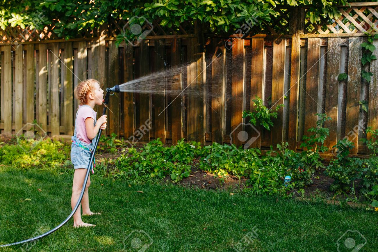 Portrait Of Girl Watering Plants Vegetables With Gardening House ...