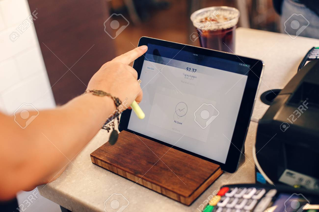 Closeup shot of young caucasian female woman cashier hands. Seller using touch pad for accepting client customer payment. Small business of coffee shop cafeteria. - 83997286