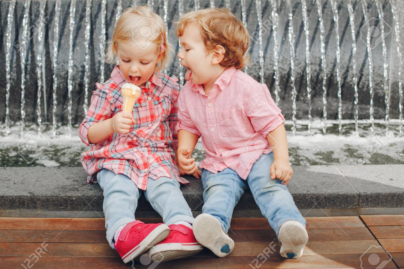 Group portrait of two white Caucasian cute adorable funny children toddlers sitting together sharing ice-cream food. Love friendship concept. Best friends forever. - 87391207