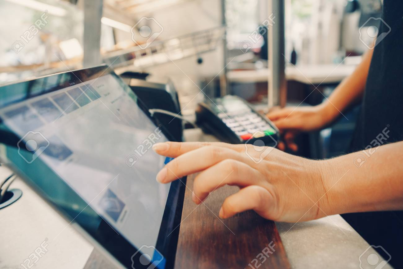 Closeup shot of caucasian cashier hands. Seller using touch pad for accepting client customer payment. Small business of coffee shop cafeteria. - 93849422