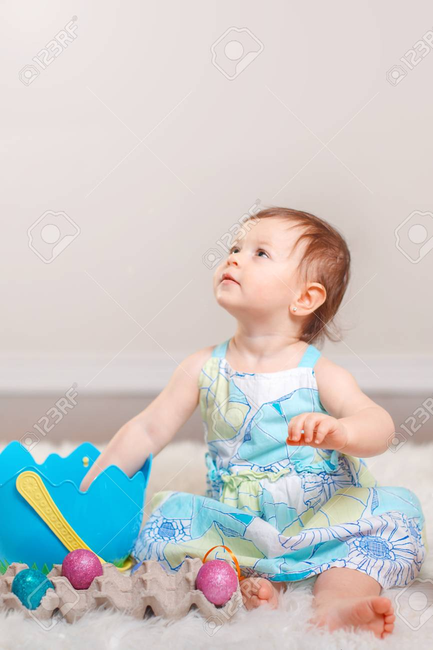 Cute adorable caucasian baby girl in blue dress sitting on white soft fluffy rug carpet in