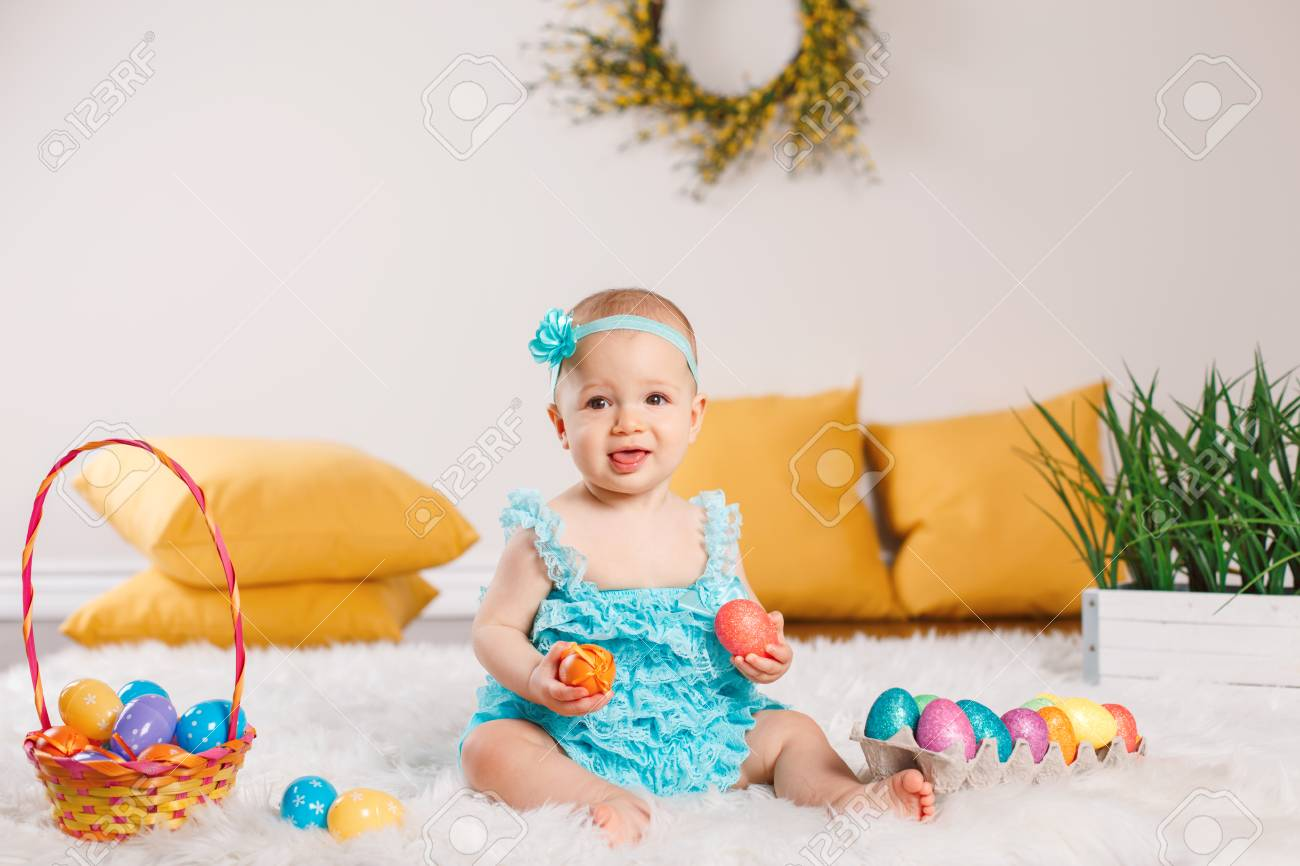 05b808fb0ec Cute adorable Caucasian baby girl in blue green romper sitting on white  soft fluffy rug carpet