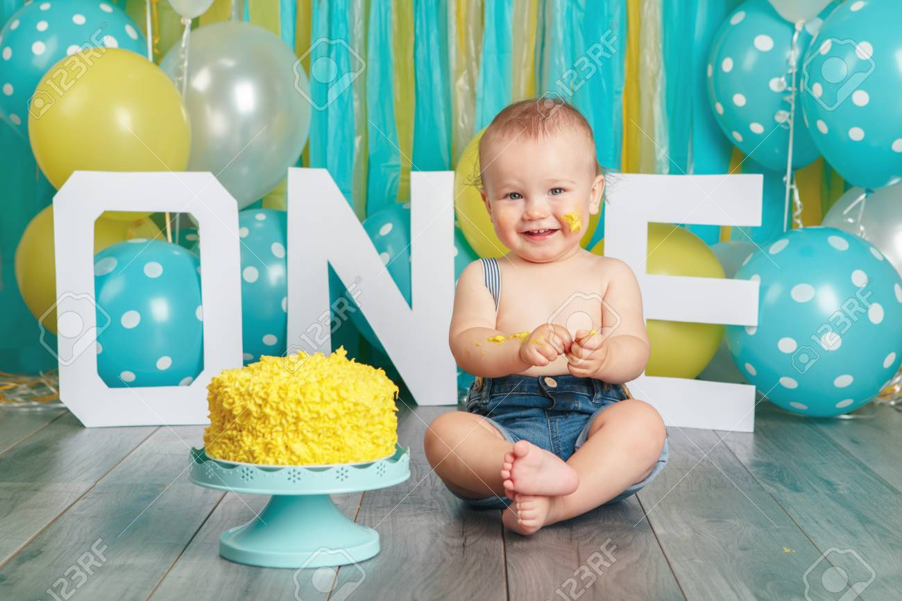 Portrait of cute adorable Caucasian baby boy in jeans pants celebrating his first birthday. Cake smash concept. Child kid sitting on floor in studio eating tasty yellow dessert - 101789976