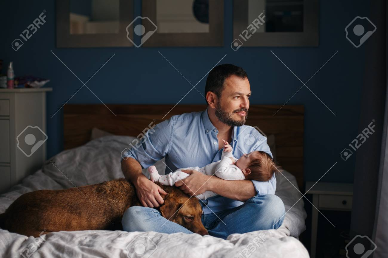 Portrait of middle age Caucasian father with newborn baby. Dog pet laying on bed. Man parent holding child in hands. Authentic lifestyle documenatry moment. Single dad family life. - 116427346