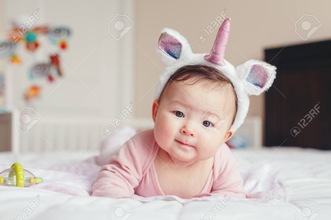 Portrait of cute adorable Asian mixed race smiling baby girl four months old lying on tummy on bed in bedroom wearing unicorn headband horn and ears looking in camera. - 119274637