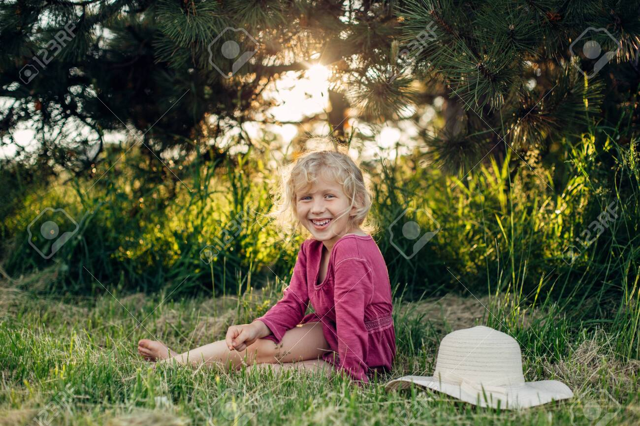 Portrait of cute beautiful blonde Caucasian girl in red pink dress with messy untidy hair sitting on ground grass in park outdoor at sunset. Happy adorable barefoot child kid enjoying summertime. - 125263474