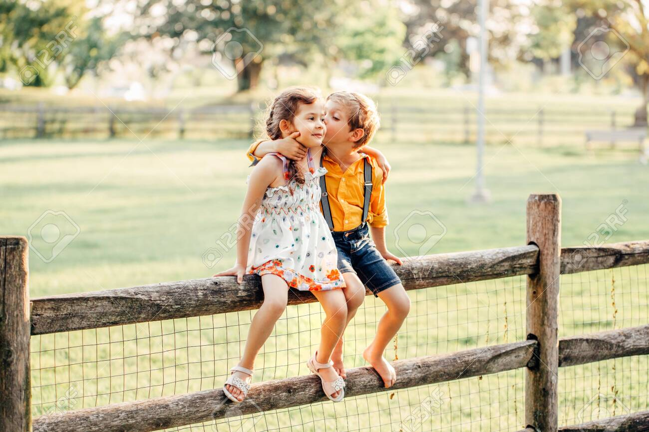 Two cute funny Caucasian children boy girl sitting on fence in park outside. Friends siblings kids hugging kissing at summer sunset. Romantic love and friendship natural lifestyle authentic moment. - 128447376