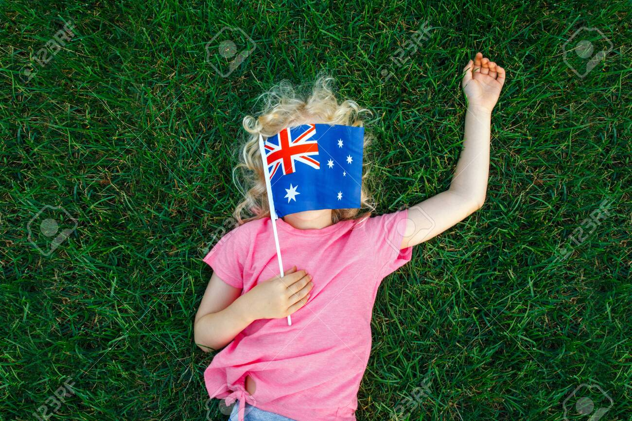 Adorable cute happy Caucasian girl holding Australian flag. Funny child kid covering her face with Australia flag. Little citizen celebrating Australia Day holiday in January outdoor. - 152543368