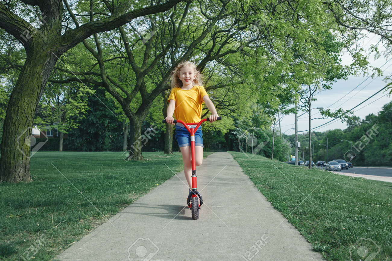 Cute funny Caucasian girl child in yellow t-shirt riding red scooter on street road park outdoor. Summer fun eco friendly sport activity for kids children. Authentic real candid childhood lifestyle. - 170913630