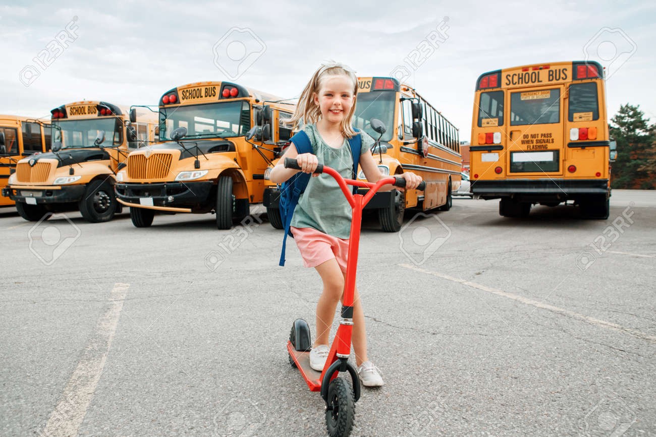 Funny smiling happy Caucasian girl kid child with backpack riding scooter on school yard by yellow buses. Education and back to school in September. Kid getting back returning to school. - 172752796