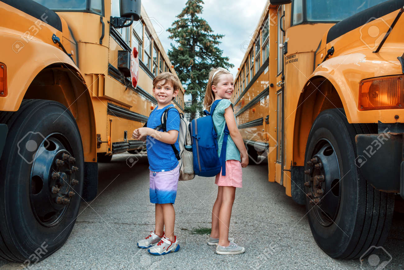 Happy Caucasian children boy and girl kids students standing by yellow school bus. Education and back to school in September. Friends schoolmates classmates meeting after summer break. - 172753190