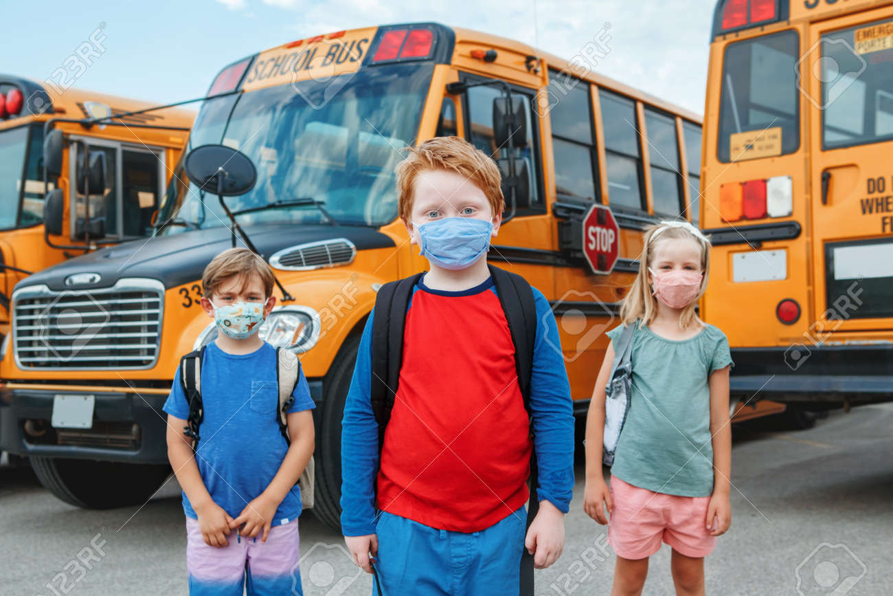 Three children kids students in protective face masks near school yellow bus outdoors. New normal at virus pandemic. Measurements against virus spread in class. - 173162761