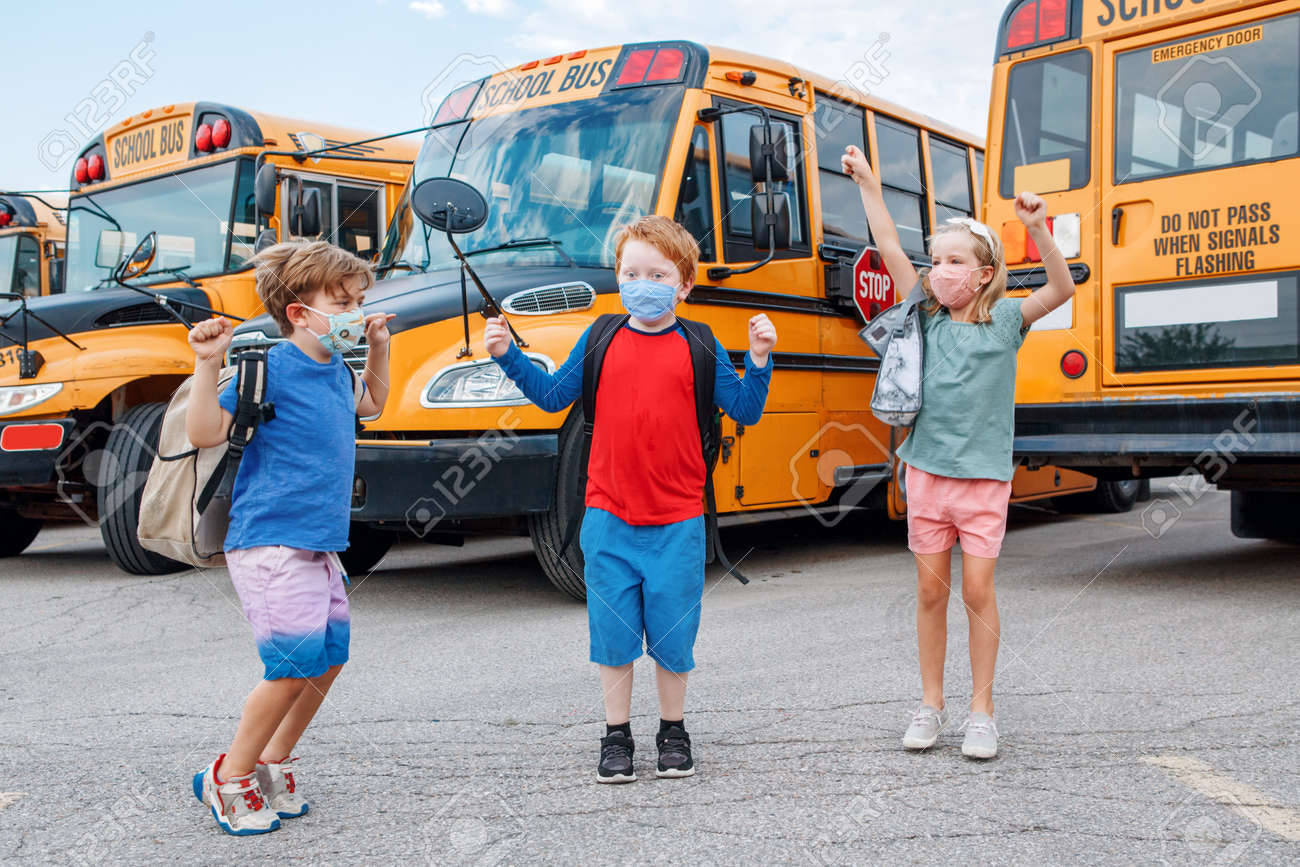 Happy excited children kids students in protective face masks jumping near school yellow bus outdoors. Back to school. New normal at virus pandemic. - 173162790