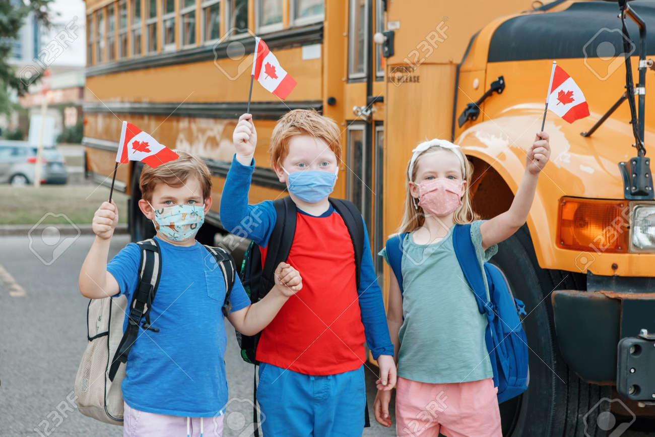 Proud happy students children with face masks holding Canadian flags. Education and back to school of kids classmates in September. New normal during virus in Canada. - 173162796