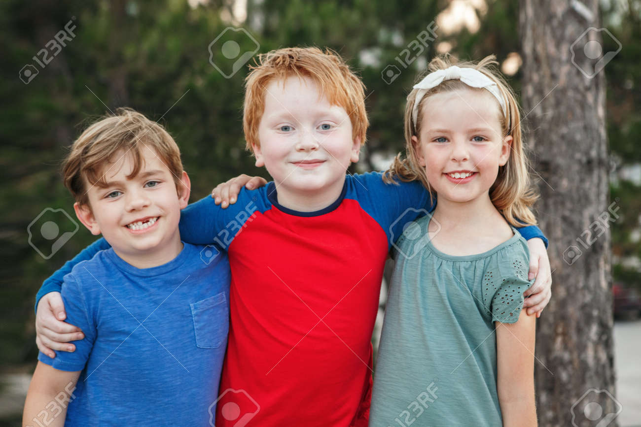 Three happy Caucasian little children kids boys and girl hugging together outdoor in park. Group of smiling friends. Best friends forever. Friendship concept. - 172753345