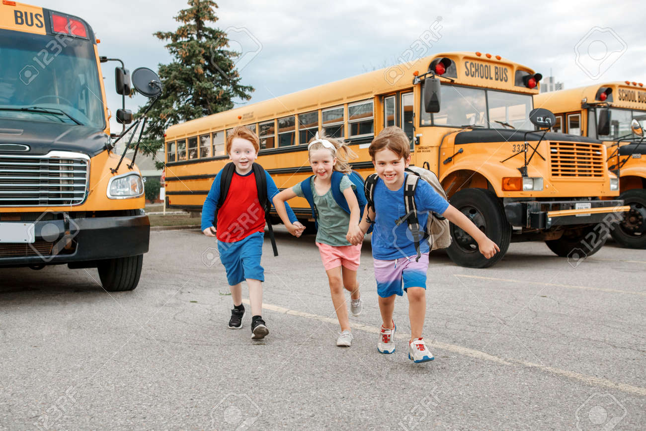 Happy Caucasian children boys and girl kids students running near yellow school bus. Education and back to school in September. Friends schoolmates classmates meeting after summer break. - 172752788