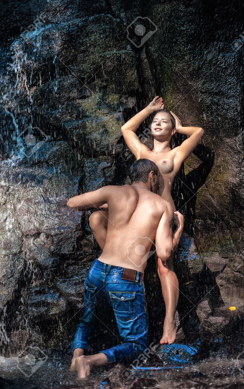 couple hugging and kissing under waterfall stock photo picture and