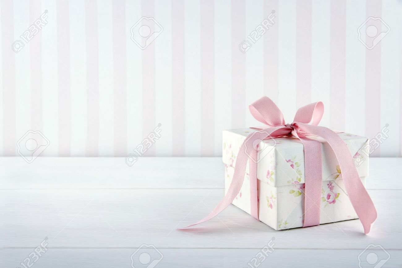 Floral pattern gift box tied with pink ribbon on white wooden background with copy space Stock Photo - 19264073