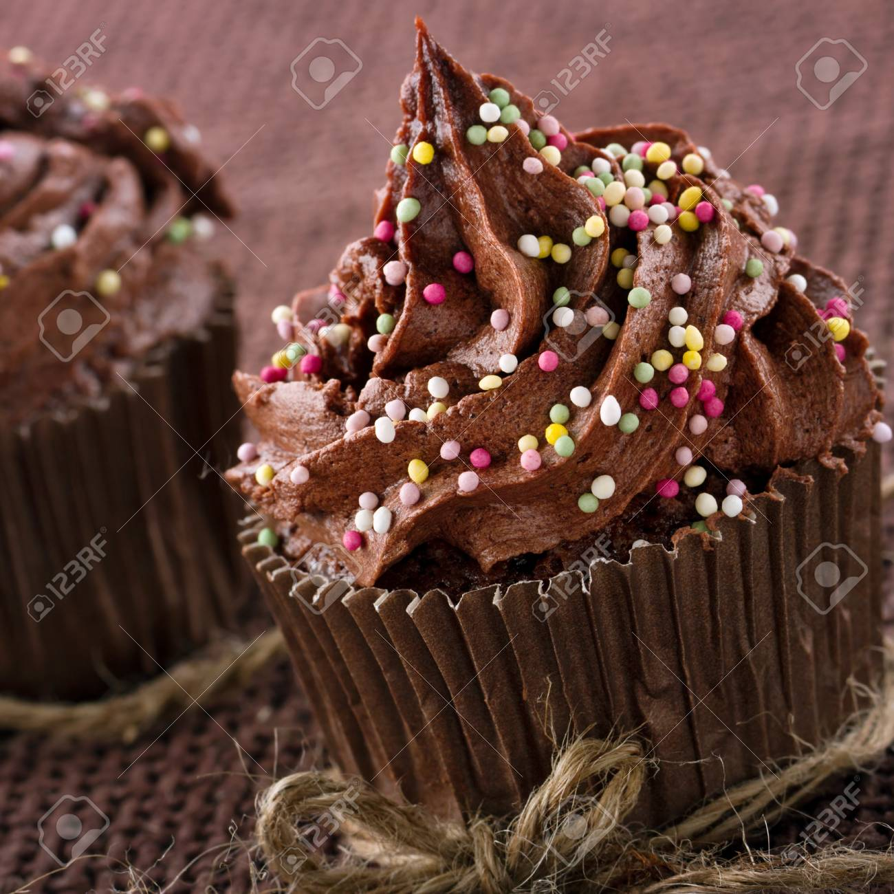 Chocolate Cupcakes With Colorful Sprinkles On Dark Background Stock