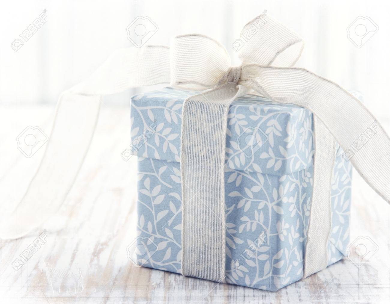 Light Blue Floral Gift Box Tied Up With White Ribbon And Pink Flower On Rustic Wooden