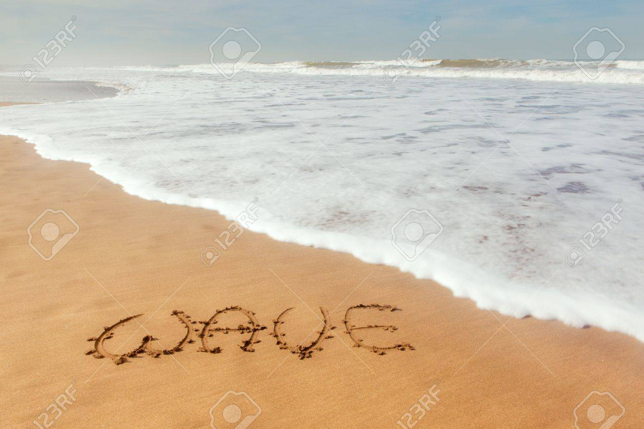 single word wave written on sand with ocean waves flowing stock