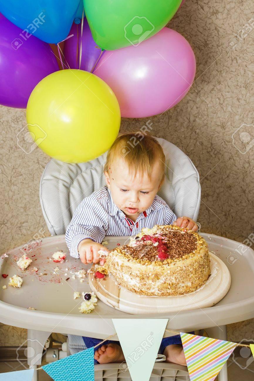 Ein Einjahriger Junge Sitzt Auf Hochstuhl Und Schmeckt Seinen Kuchen