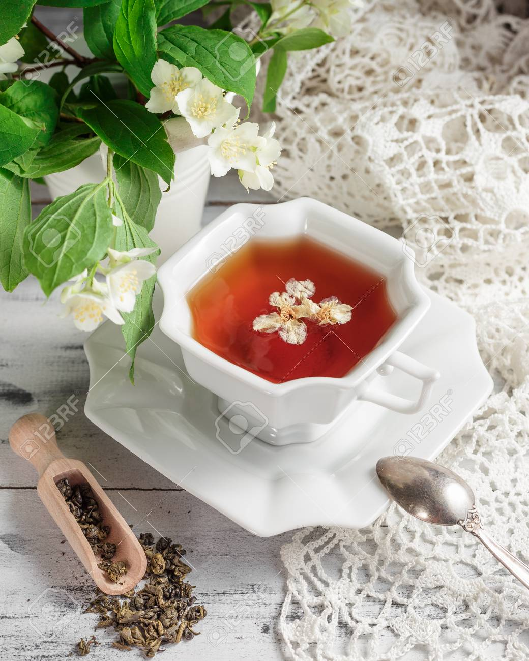 White Porcelain Cup Of Tea With Jasmine Flowers Scattered Dry
