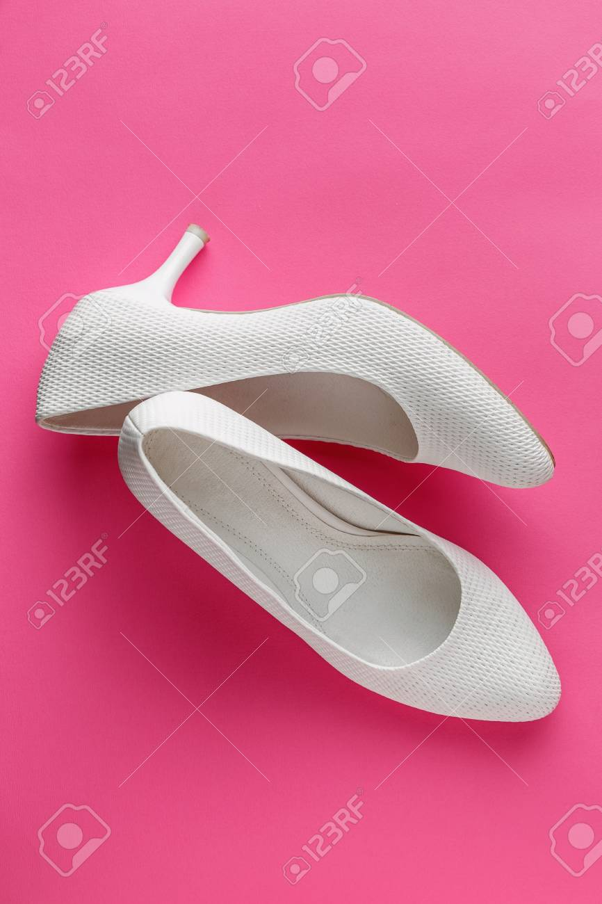 f18fd8e80d0b0 Simple white wedding shoes on pink background Stock Photo - 102412858